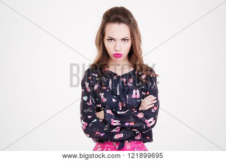 Angry offended young woman standing with arms crossed over white background
