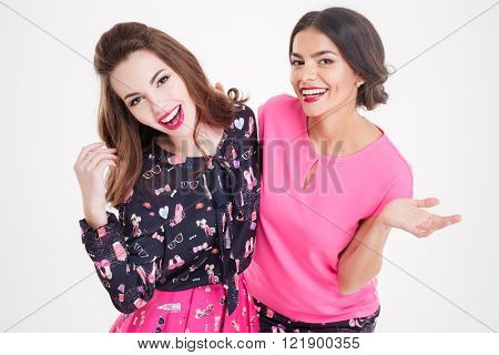 Portrait of two happy pretty young women standing and hugging over white background