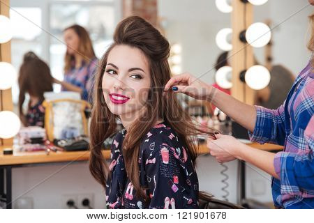Female hairdresser standing and making hairstyle to cute lovely young woman in beauty salon