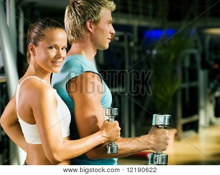 Fitness couple in the gym, rivaling each other, exercising with weights (focus on the face of the girl) poster