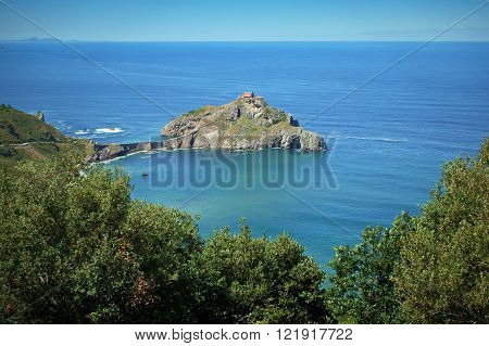 Postcard of the iconic monsatery of San Juan de Gaztelugatxe, raising from the sea in a secluded island, connected to the main land by a narrow and winding cobble stone path.