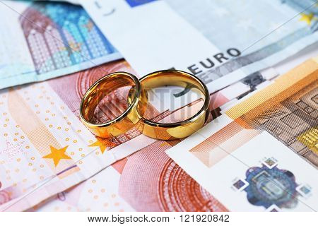 Golden wedding rings on euro banknotes background. Marriage of convenience