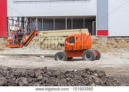 Worker is driving the cherry picker across building site