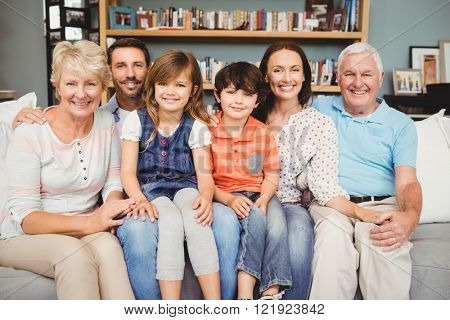 Portrait of smiling family sitting on sofa at home