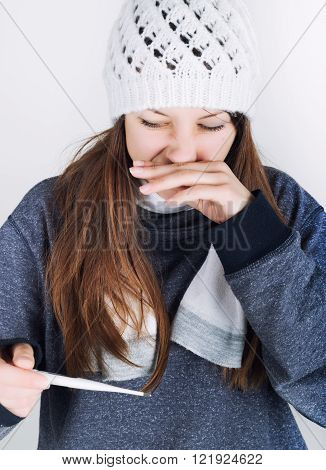 young woman in a knitted hat and scarf, holding hands in the thermometer. she seems sick, scratching