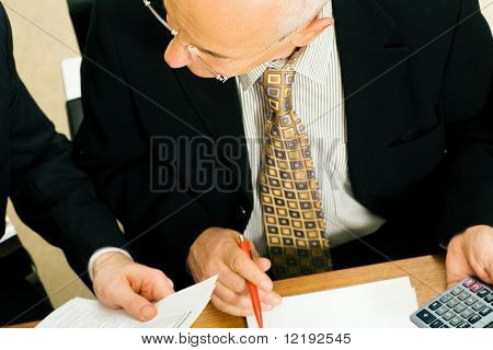 Two businesspeople discussing a draft of a contract