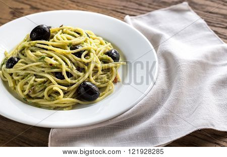 Portion of pasta with guacanole and black olives