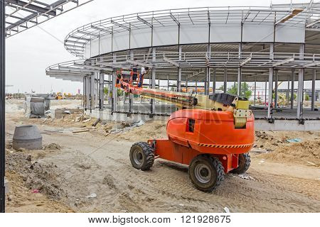 High elevated cherry picker with team of workers on construction site.
