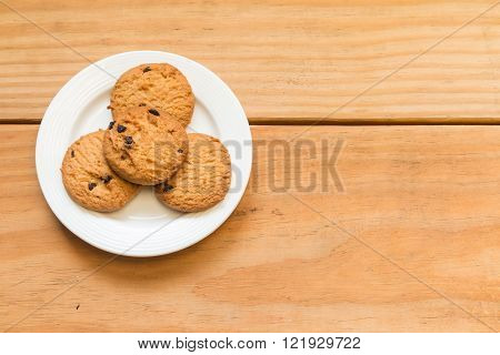 Chocolate chips cookies on the white dish with free space in right side