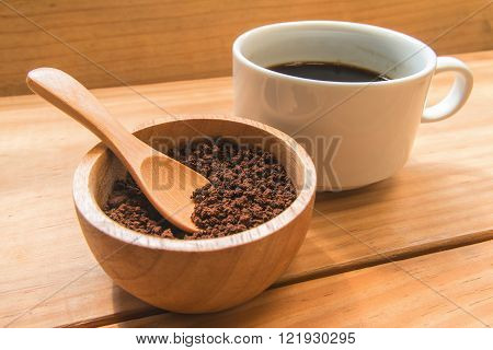 Instant coffee in the wood bowl with white cup of coffee focus at instant coffee