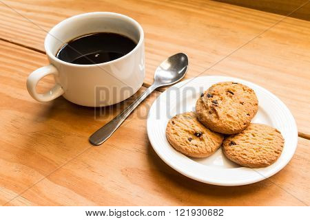 White cup of coffee with chocalate chips cookies in white dish focus at edge of coffee cup