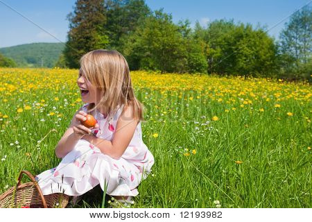 Little girl on a beautiful sunlit meadow in spring on an Easter egg hunt having just found a nest