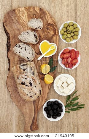 Greek antipasti with olive bread on a wooden board with feta cheese, green and black olives, leaf sprigs, lemons and oil on oak background.