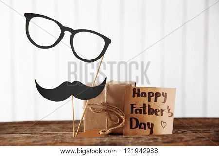 Greeting card for Happy Father's Day with paper mustache, glasses and gift box on wooden table