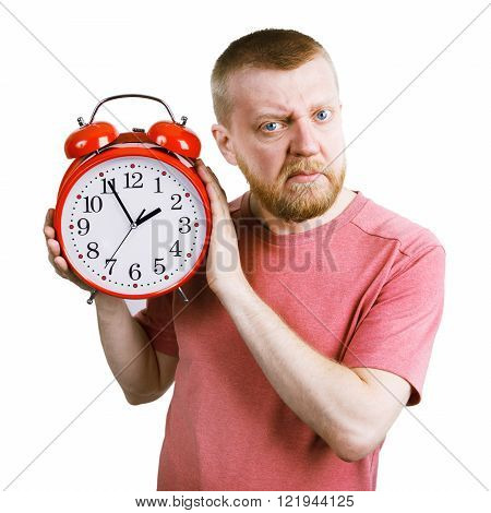 Unhappy bearded man with a red alarm clock in his hand