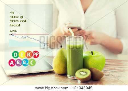 healthy eating, technology, diet and people concept - close up of woman hands holding smartphone with tablet pc, fruits and fresh juice sitting at table over calories and vitamin chart