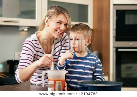 Family cooking in their kitchen - mother making some spaghetti sauce, son having a taste licking his finger for it
