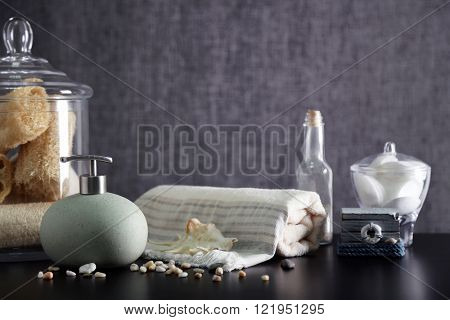 Bathroom set with dispenser, towel and wisps on grey background
