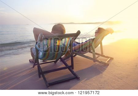 Happy couple sitting at sun chairs on the beach of Koh Samet at sunset Thailand