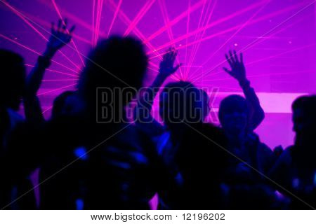 Silhouettes of dancing people having a celebration in a disco club, the light show is sending laser beams through the backlit scene, FOCUS IN ON THE BEAMS! poster