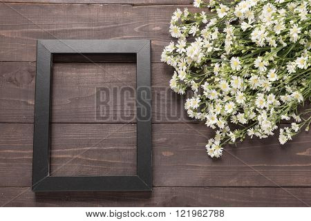 Picture frame and cutter flowers are on the wooden background.