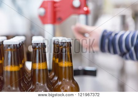 Close-up of glass bottles full of craft beer on a bottled process. Unrecognizable person on background