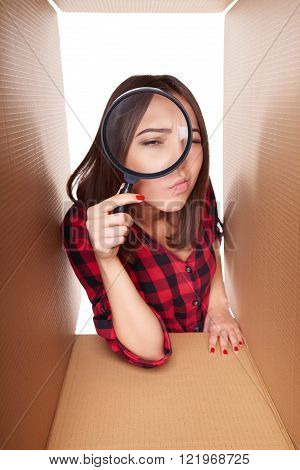 Female peeking into carton box looking through magnifying glass