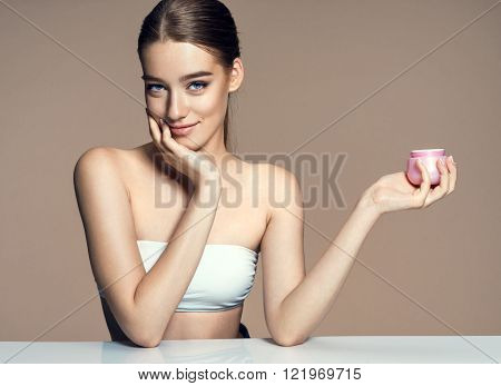 Beautiful young lady applying moisturizing creme skin care concept / photoset of attractive brunette girl on beige background