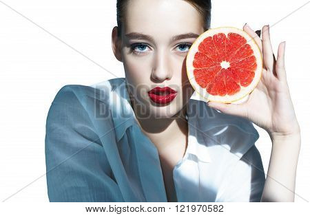 Pretty girl with grapefruit, natural organic raw fresh food concept / photoset of attractive girl holding a cut piece of Sicilian orange on white background
