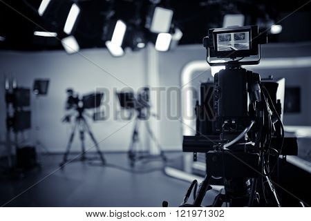 TV Studio live broadcasting.Recording show.TV NEWS program studio with video camera lens and lights.Positioned stage big professional broadcasting camera with headphones