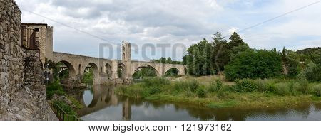 Scenic panoramic view of ancient bridge across Fluvia River in medieval town Besalu Catalonia Spain.