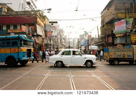 KOLKATA, INDIA - JAN 13: Antique white Ambassador car down the busy street on January 13, 2013 in Kolkata India. First Ambassador was produced by the Yellow Cab Manufacturing Company in 1921