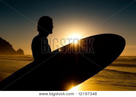 Young surfer on the beach with his surf board beside, looking at the ocean