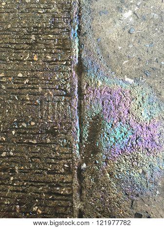 Oil leak rainbow sheen on the ground