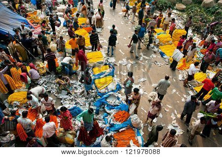 KOLKATA, INDIA - JAN 13: Sellers of yellow flowers work on crowded Mullik Ghat Flower Market on January 13, 2013 in Kolkata. The flower market is 125 years old. 2000 sellers work in it every day