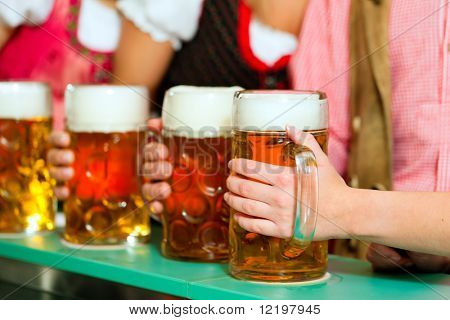 Inn or pub in Bavaria - group of young men and women in traditional Tracht having a party with beer, the steins are standing on the bar