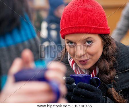 Menschen auf ein Weihnachtsfest Markt drinking Punch oder scharf gewürzt Wein, es ist kalt und sie haben eine Notwendigkeit, w