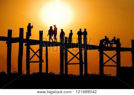 Wooden pedestrian bridge U-Bein in Mandalay (Myanmar) from passing through it people against the backdrop of the setting sun