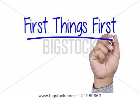 Man Hand writing First Things First with black marker on visual screen. Isolated on white. Business technology internet concept. Stock Photo