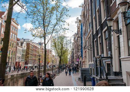 Amsterdam-April 30: Amsterdam's Red Light District tourists go sightseeing on April 302015 the Netherlands. The Amsterdam Red Light District is one of the most iconic places in all of Europe famous for its liberal laws cafes and ladies of the night.