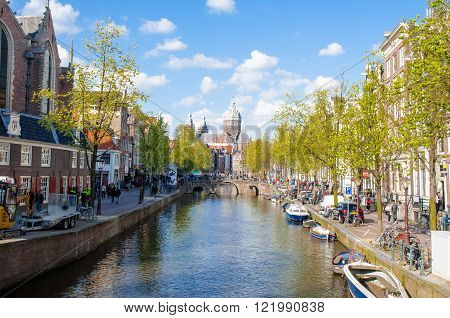 Amsterdam-April 30: Amsterdam's Red Light District crowd of tourists go sightseeing the Church of St. Nicholas is visible in the distance on April 30 2015 the Netherlands.