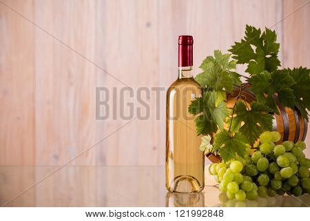 Bottle of wine with a barrel and grapes and grapeleaves