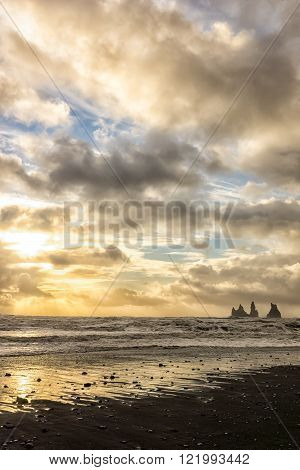 Beautiful sunset at the black sand beach by the small village Vik in south Iceland with the famous Reynisdrangar rock formation in the background.