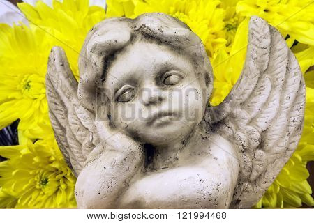 child angel or cherub day dreaming in front of yellow flowers