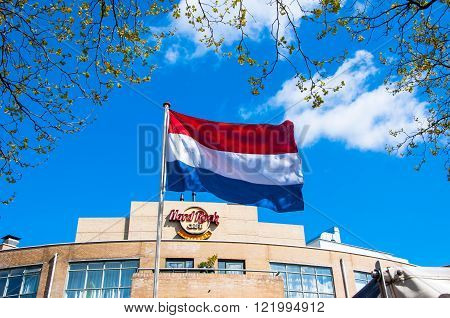 AMSTERDAM-APRIL 30: Holland flag and Hard Rock Cafe signage on the backgroud on April 302015. Hard Rock Cafe Amsterdam offers an immersive experience in the waterside restaurant and cocktail bar.