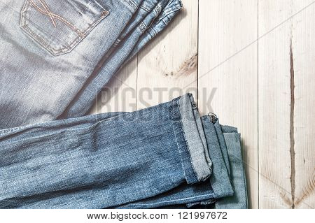 Blue jeans on a wooden background.Frayed jeans on a rough wood surface.