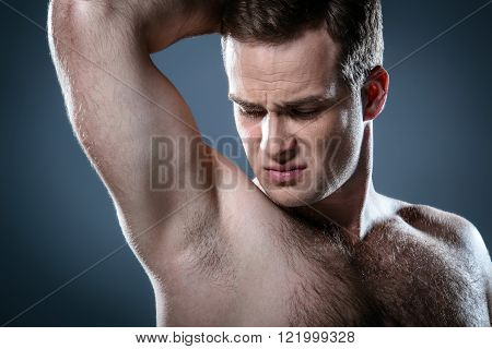 Studio portrait of handsome young man. Clean shaven man with naked torso looking at armpit