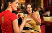 Two young women having coffee break together poster