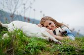 Girl with her dog resting outdoors poster