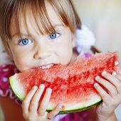 Funny child eating watermelon closeup poster